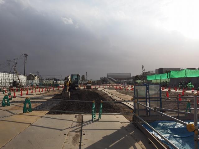 左側によって同方向。バックホウが地面をならしています。画面左側の工事用通路に注目。