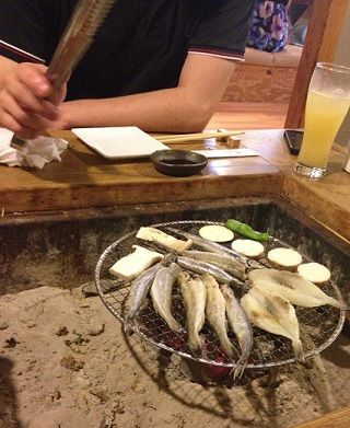 炉端で魚を焼く