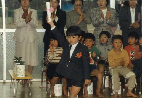 埼玉県秩父市に生まれる。実家は旅館経営をしており、幼少期から商業が身近にある環境にあった。小学校6年生の時に、埼玉の大宮市に引っ越すが、言葉の訛りや性格が