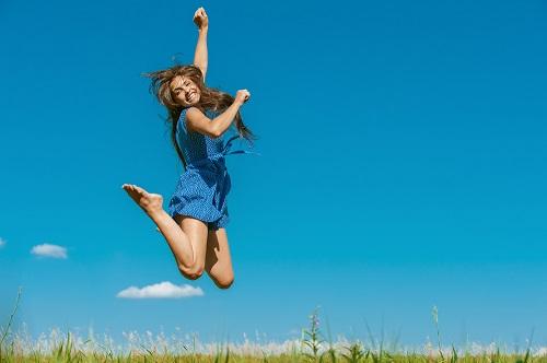 woman-outside-in-field-jumping-in-air-blue-dress.jpg